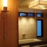 Интересно централно осветително тяло и акцентиращи вертикални лампи около огледалото