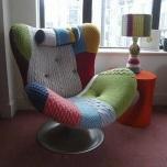 Облечен със стари разноцветни пуловери стол